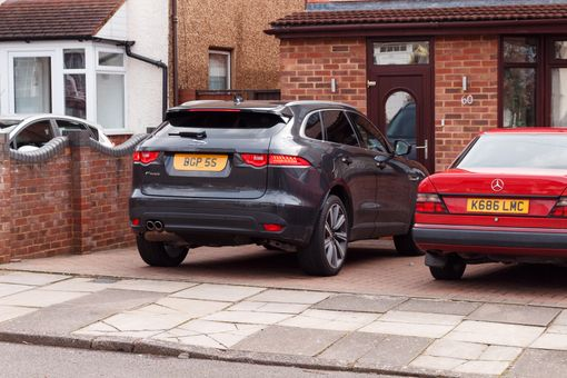 Two cars parked in UK driveway. Two-car households are increasing.
